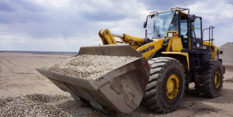 A front-end loader with a bucket filled with rock
